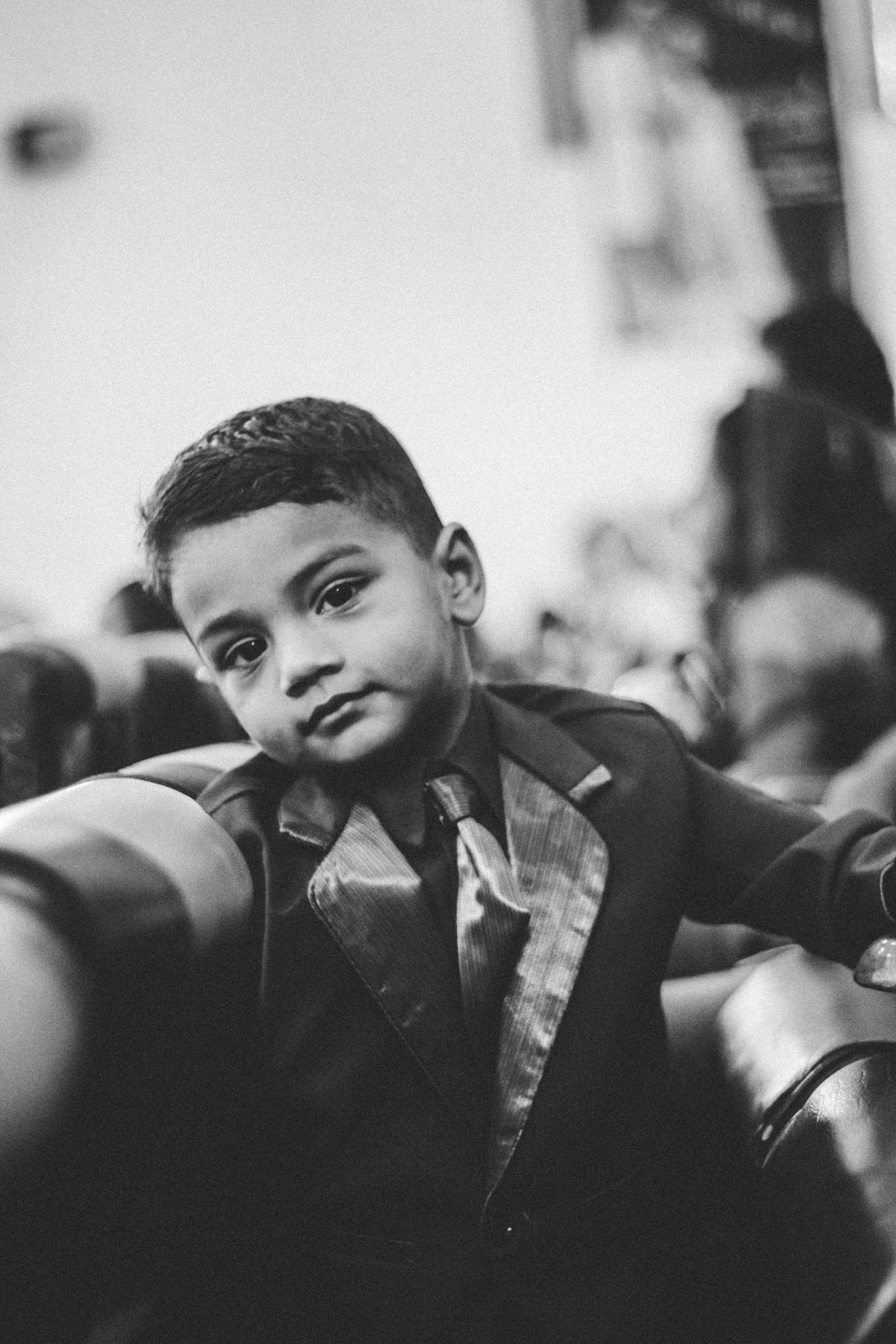 grayscale photography of smiling boy in formal suit jacket