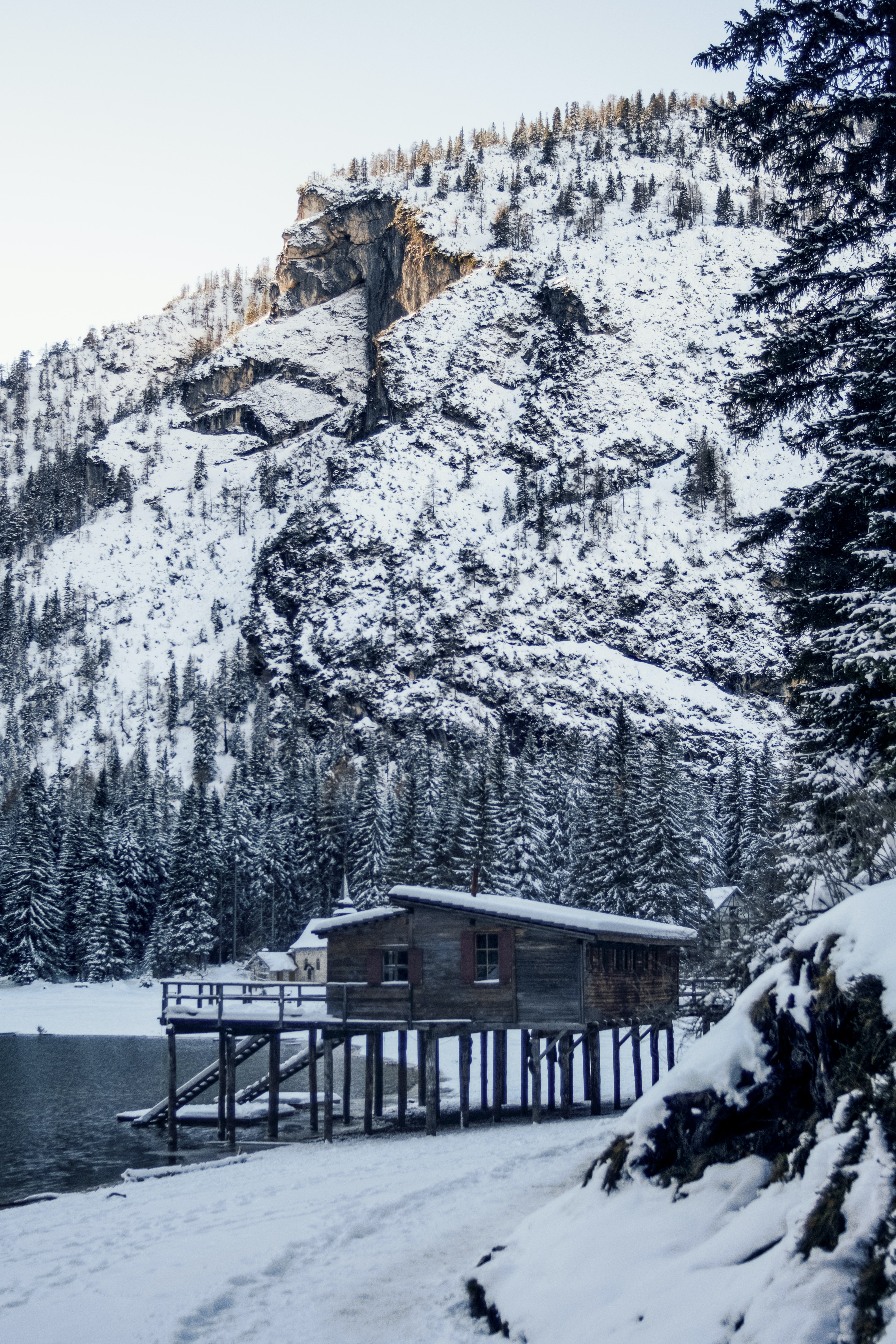 brown wooden house beside body of water near mountain covered by snow