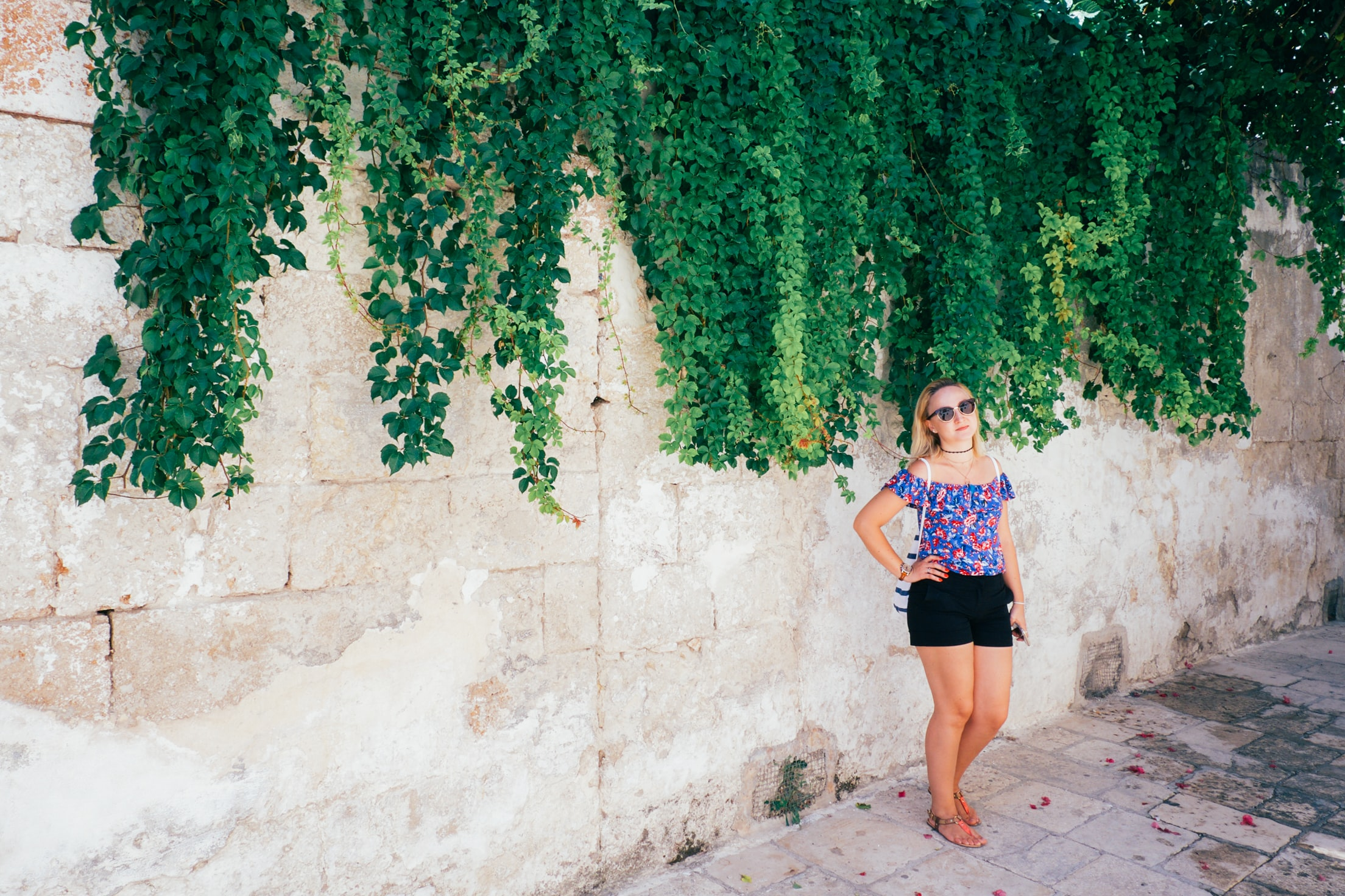 woman holding her waist while standing beside white concrete fence with vine plants