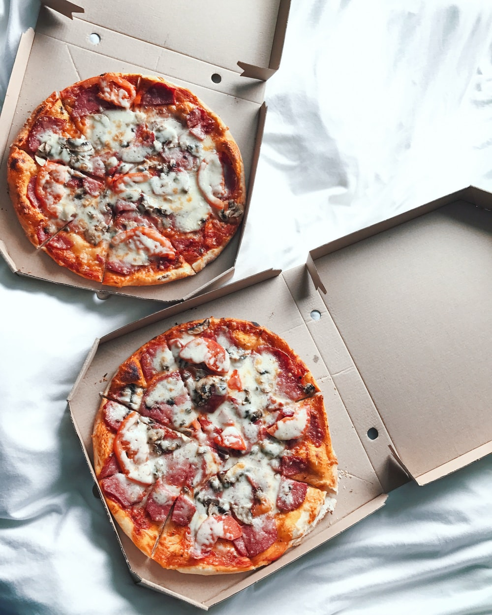 two pizzas on boxes