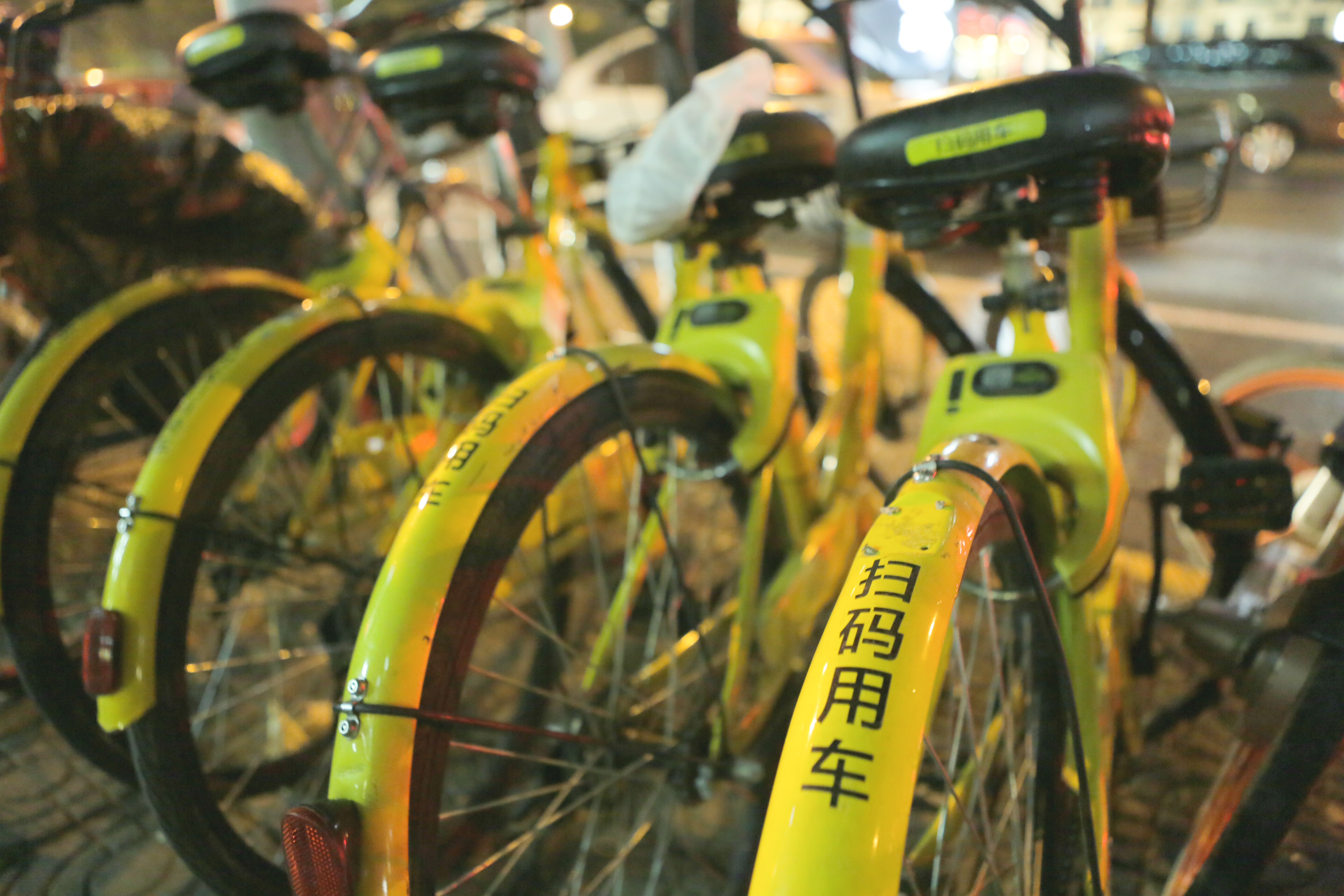 four yellow bike parked beside the road