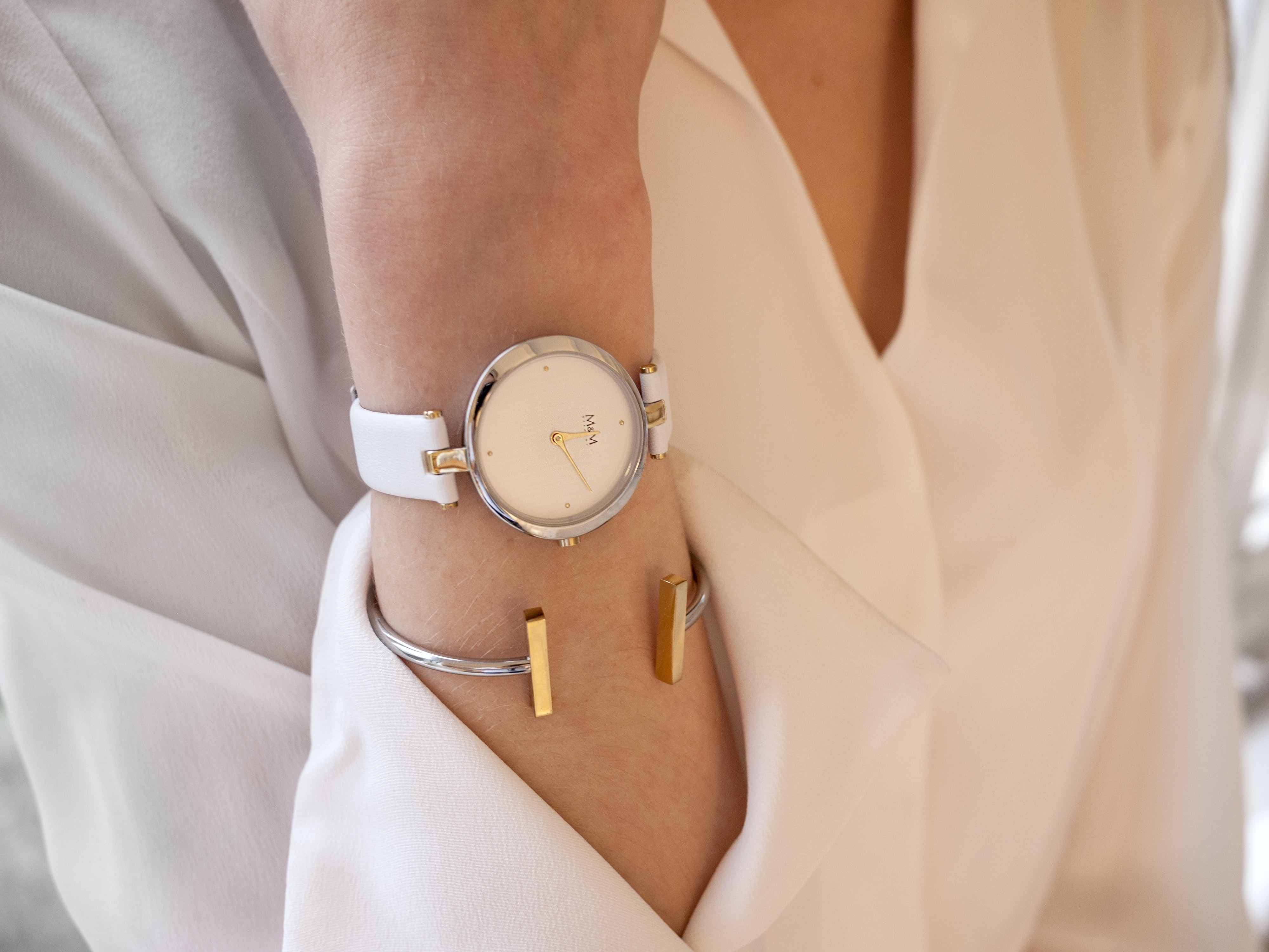 close-up photo of woman in white top wearing watch
