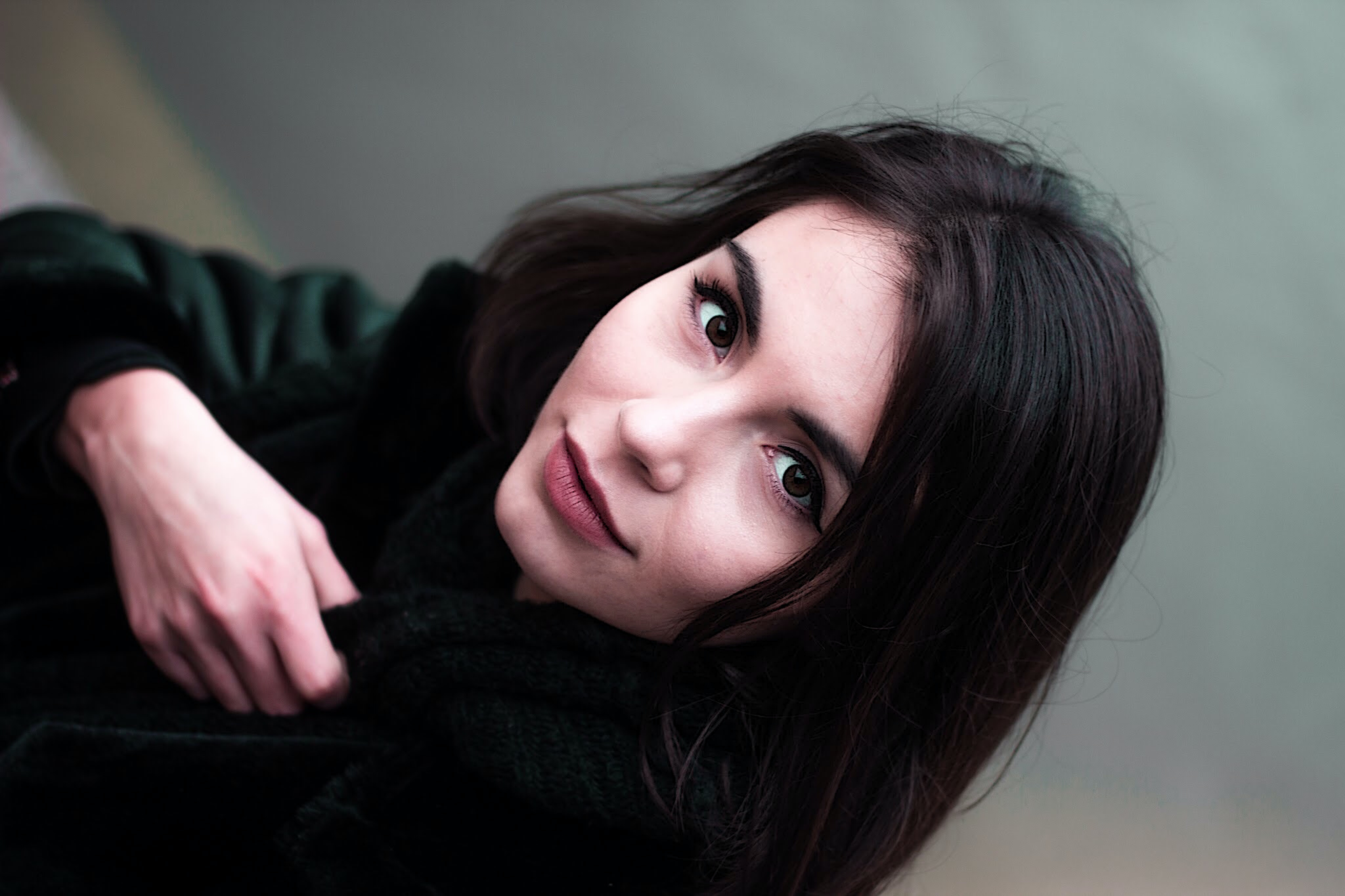 shallow focus photography of woman showing smile while holding coat
