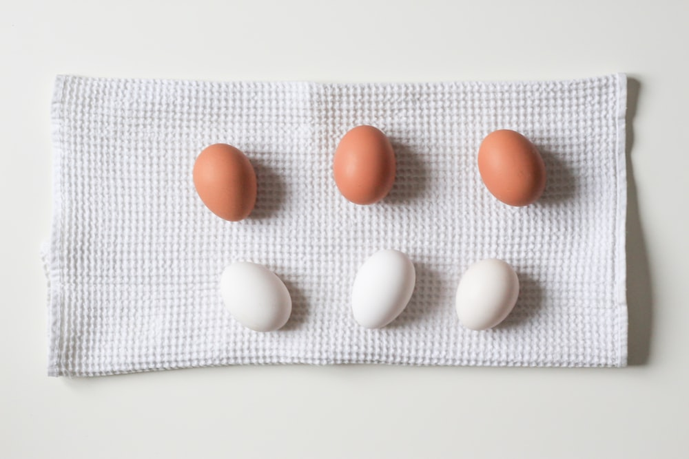 six white and brown eggs on white towel