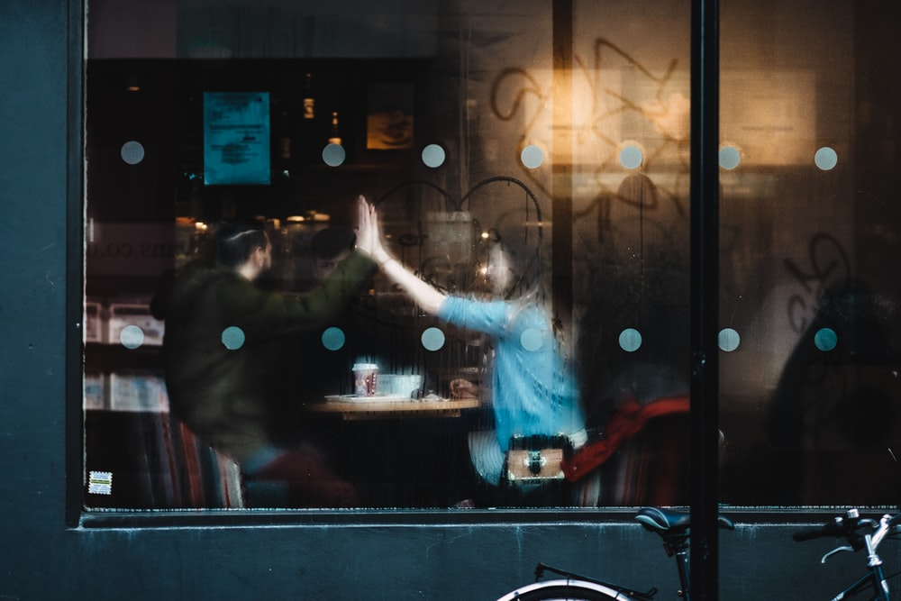 man and woman clapping each other hands inside the cafe