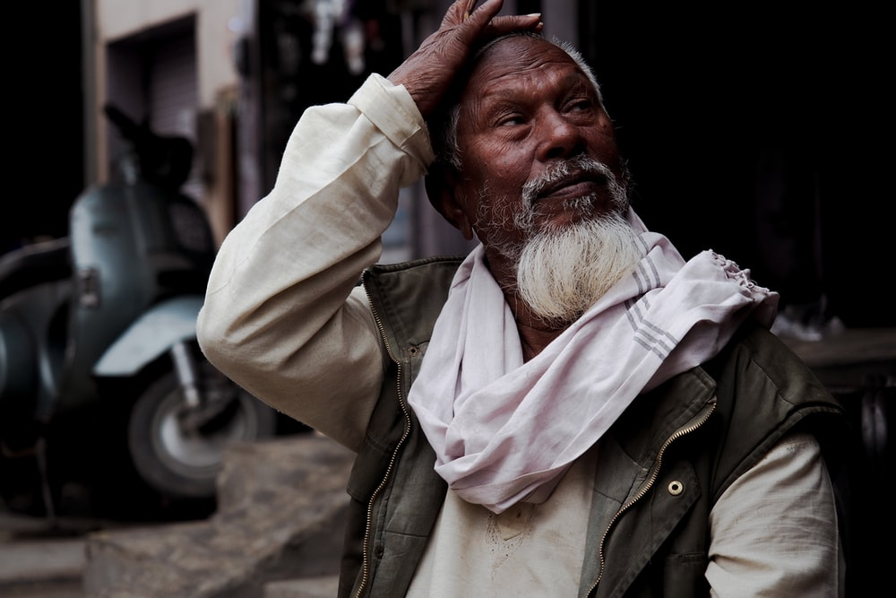 man with white scarf touching his forehead