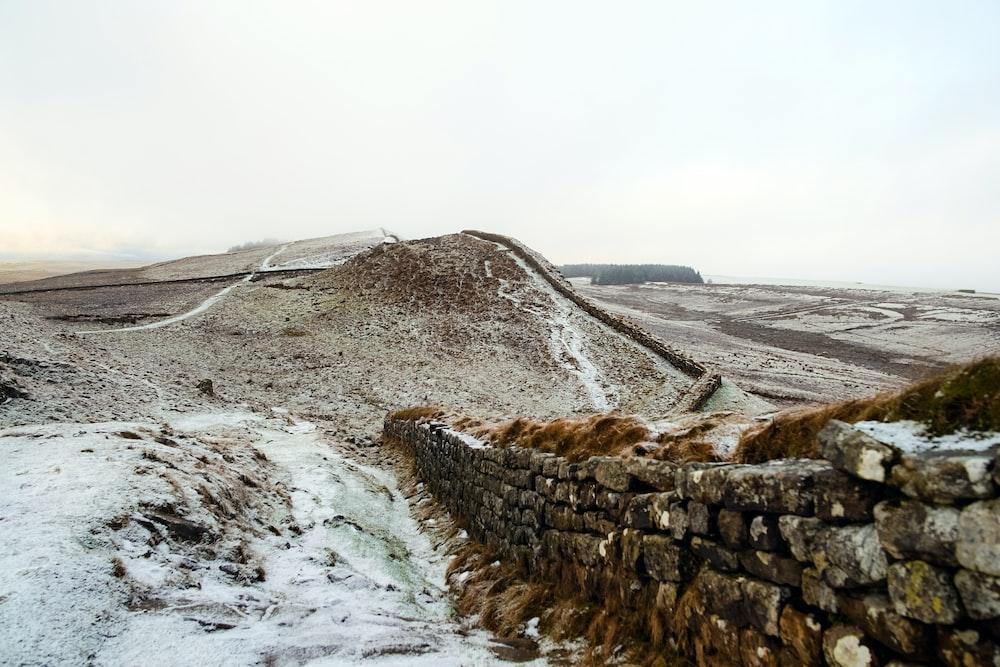 landscape photography of grey bricked wall near mountain