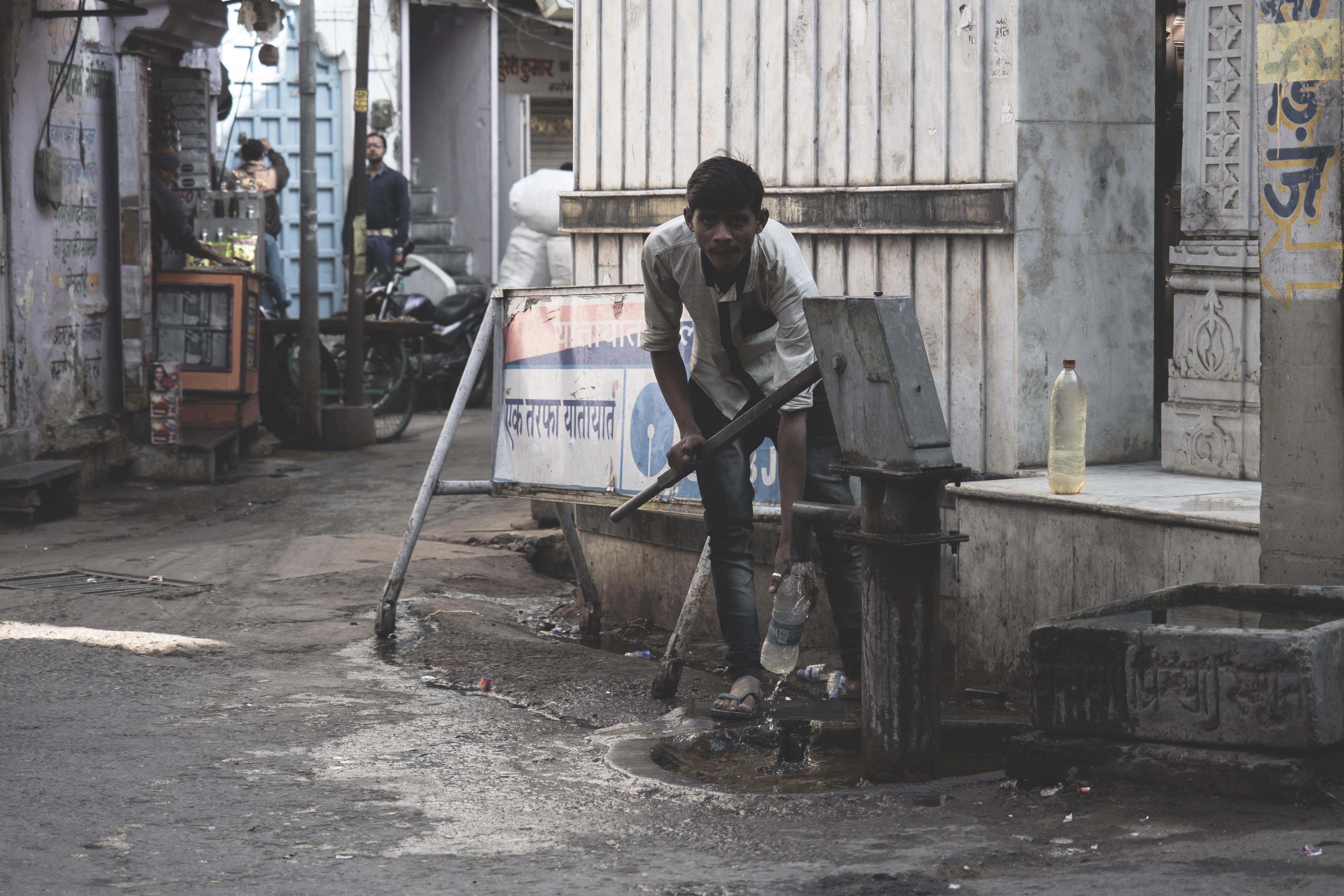 man pumping water on water pump