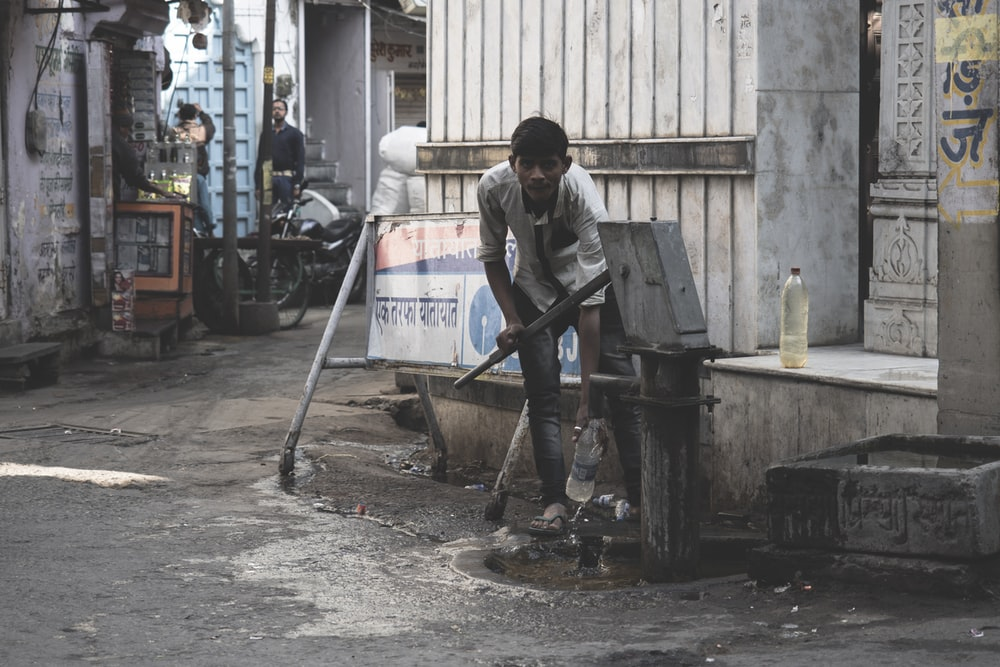 man pumping water on water pump