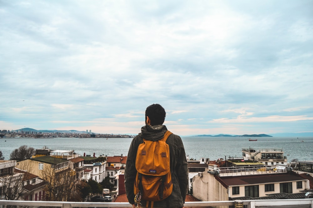 man carrying orange backpack looking at the houses near ocean