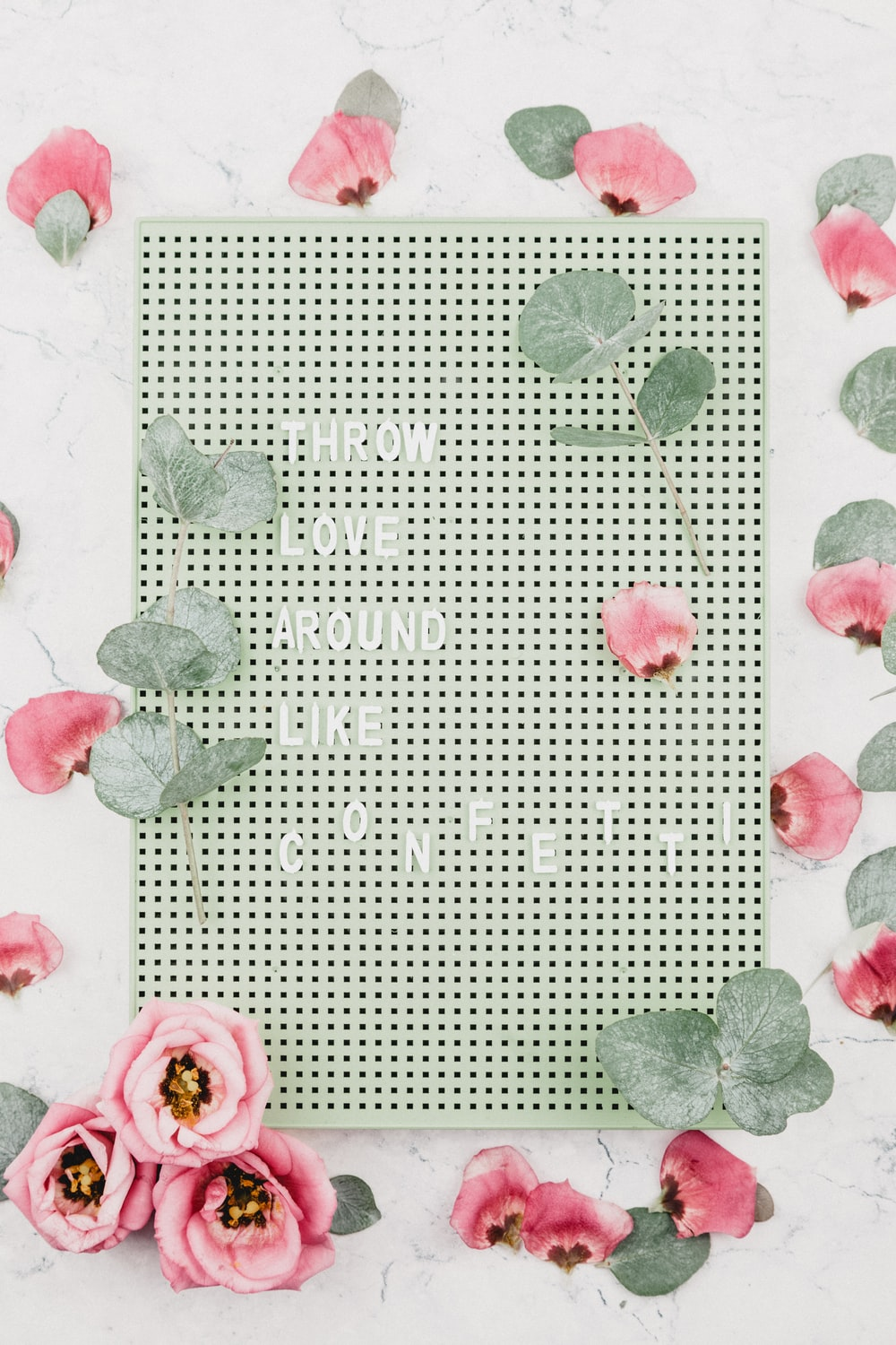 throw love around like confetti text on board surrounded b y flowers