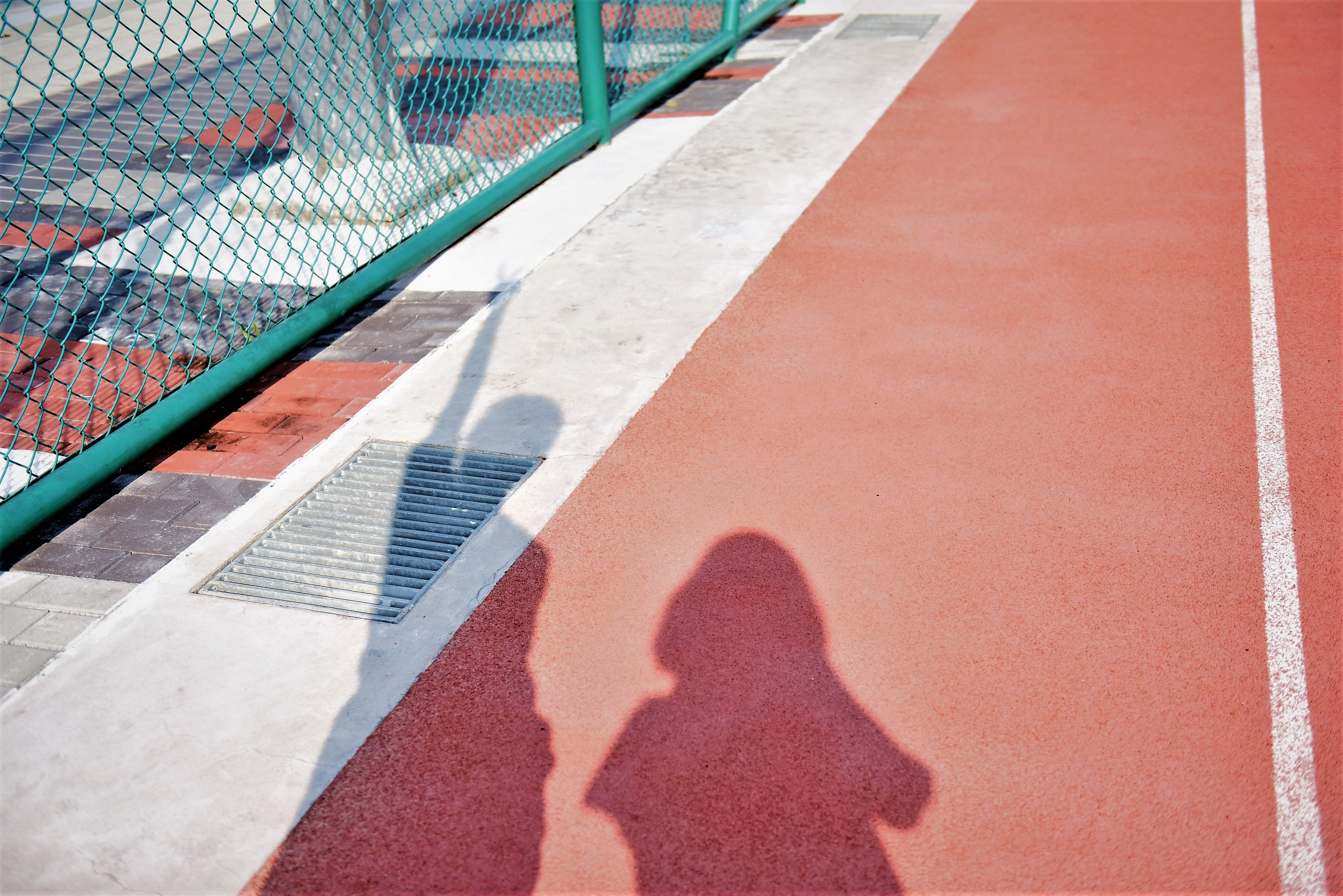 two person's shadow on brown and red surface