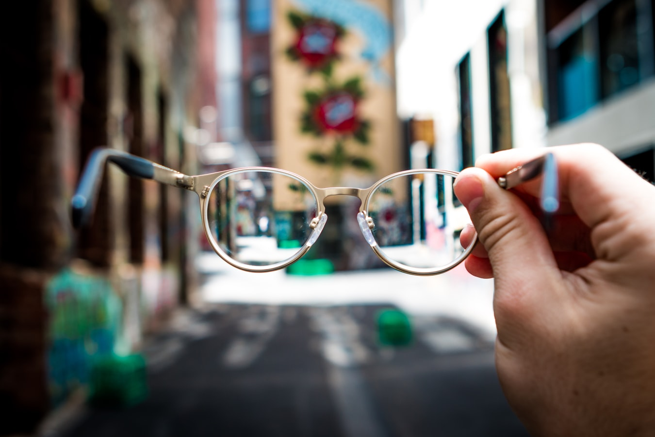 A pair of glasses looking at an out of focus neighborhood