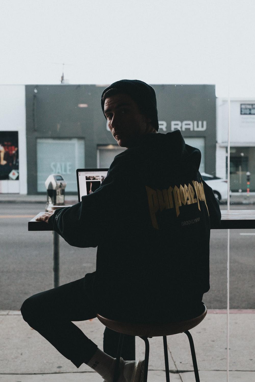 man sitting in stool using a laptop
