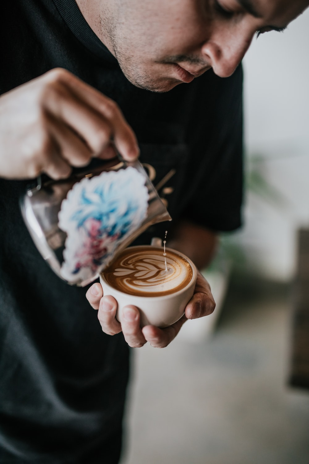 person holding mug and making cappuccino