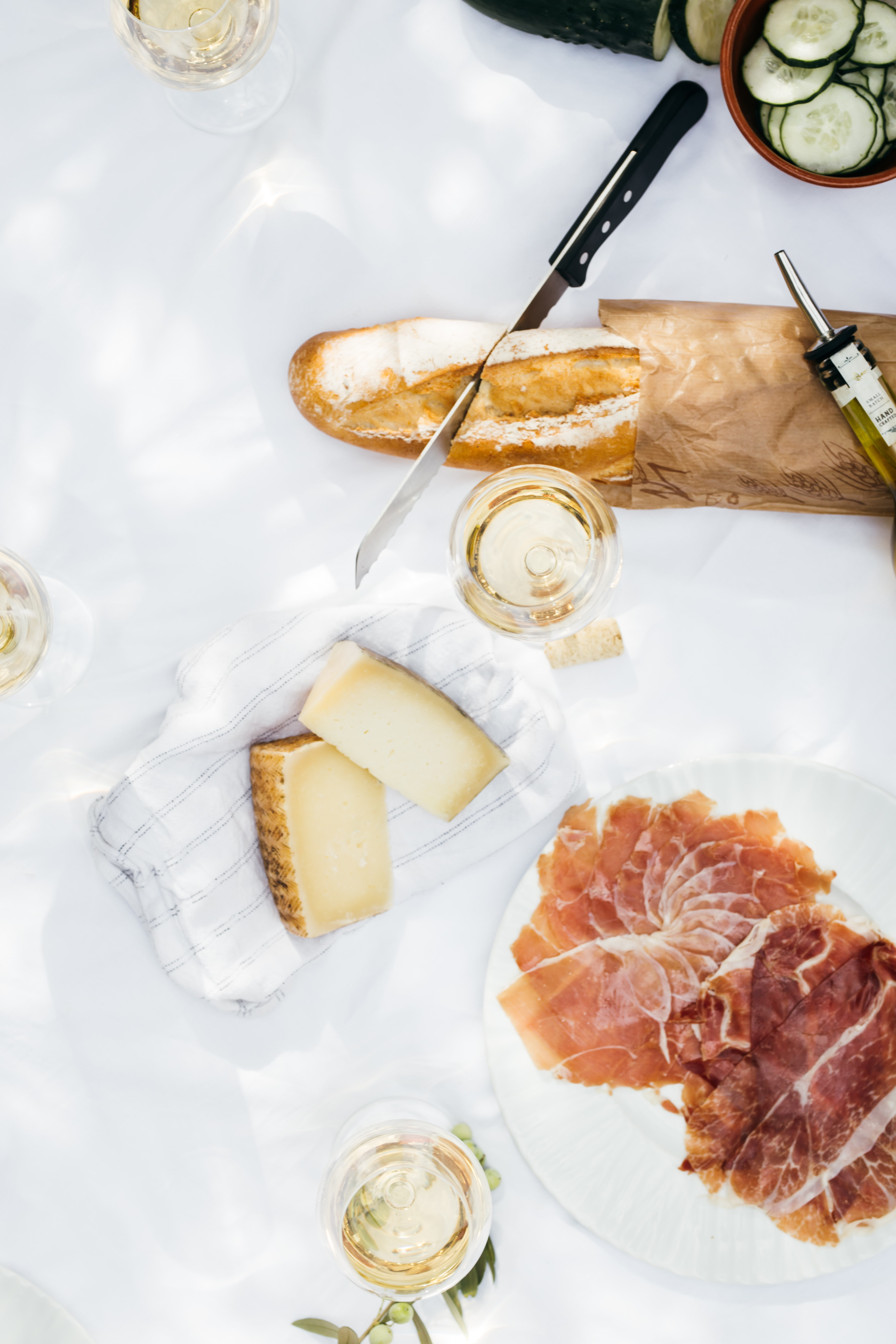 flat lay photography of cheese near jar filled with clear liquid next to bread