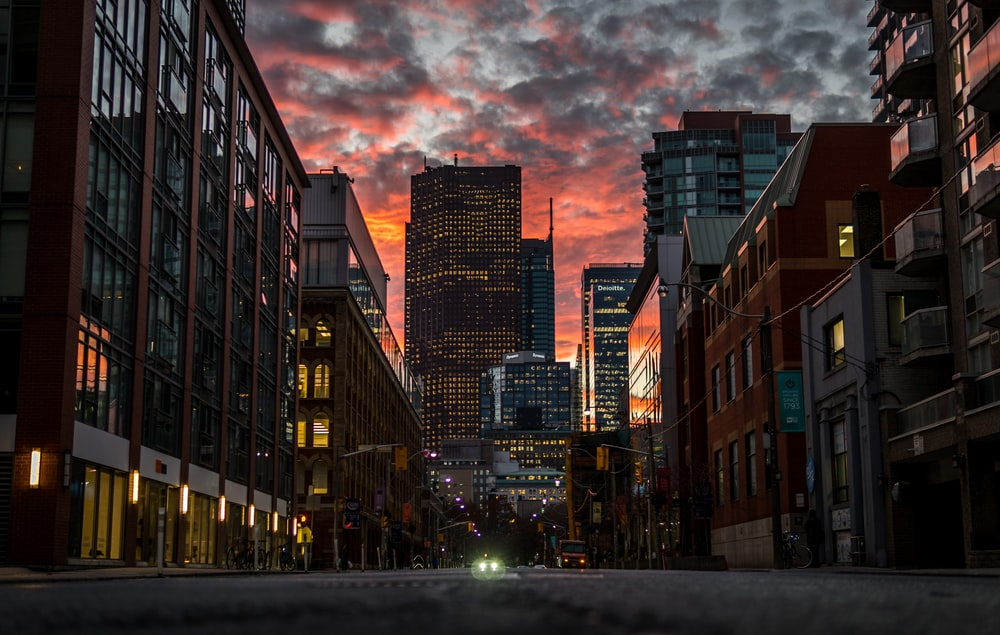 city buildings under gray clouds during sunset
