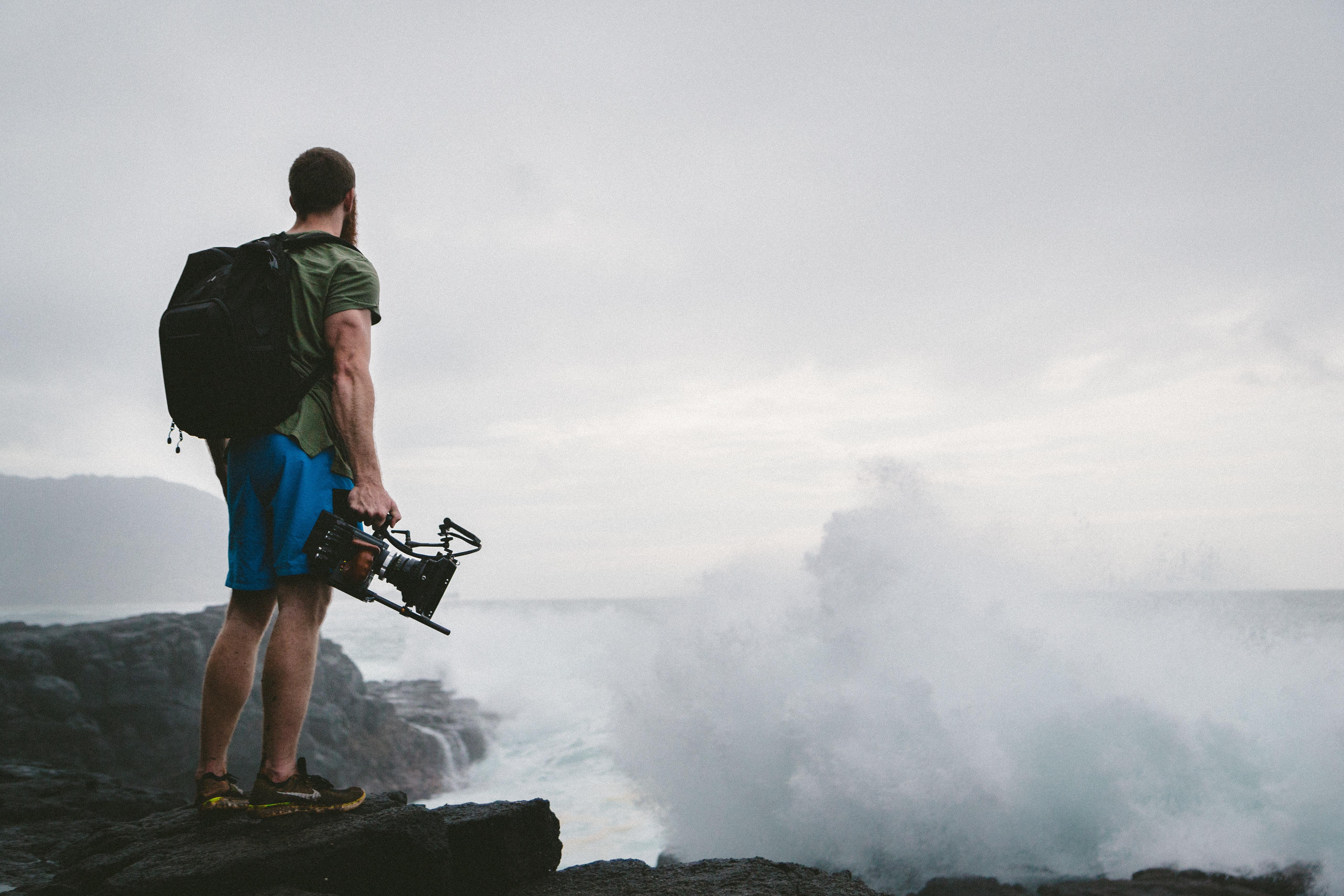man in green shirt standing near clouds