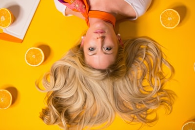 photo of woman leaning on yellow surface hair teams background