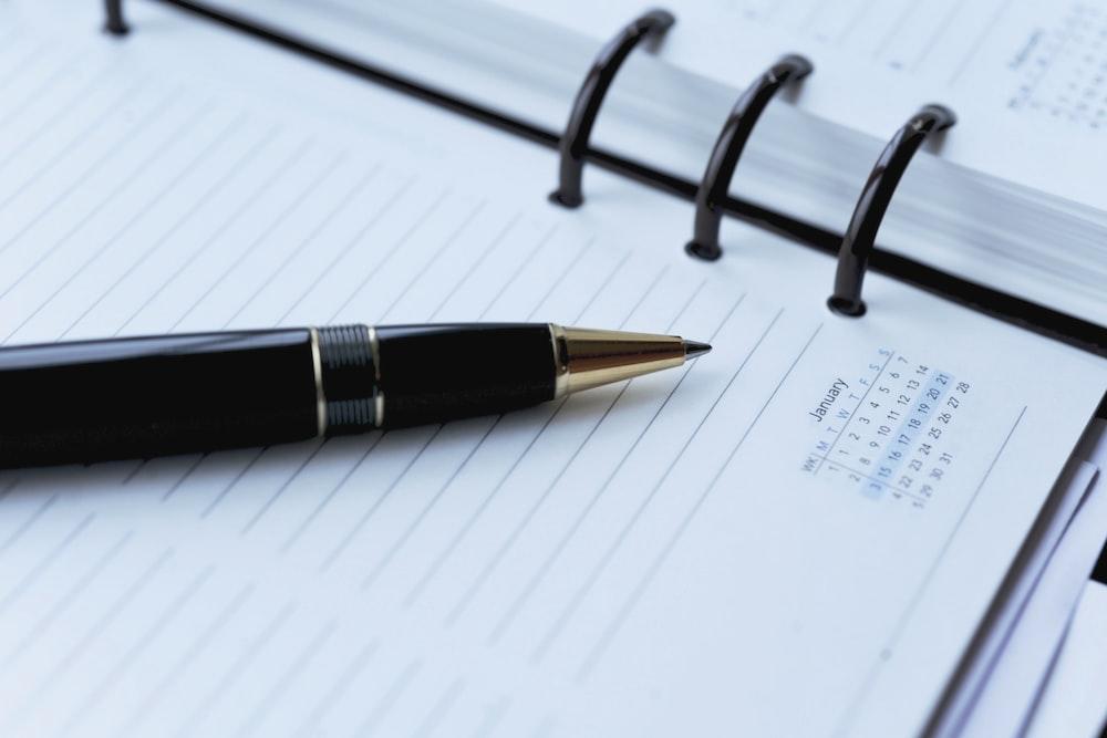 black ballpoint pen on white spiral notebook