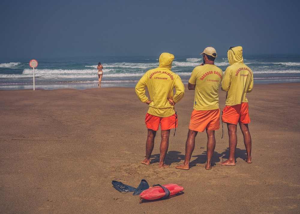 three men standing on brown sand starring in woman standing at seashore