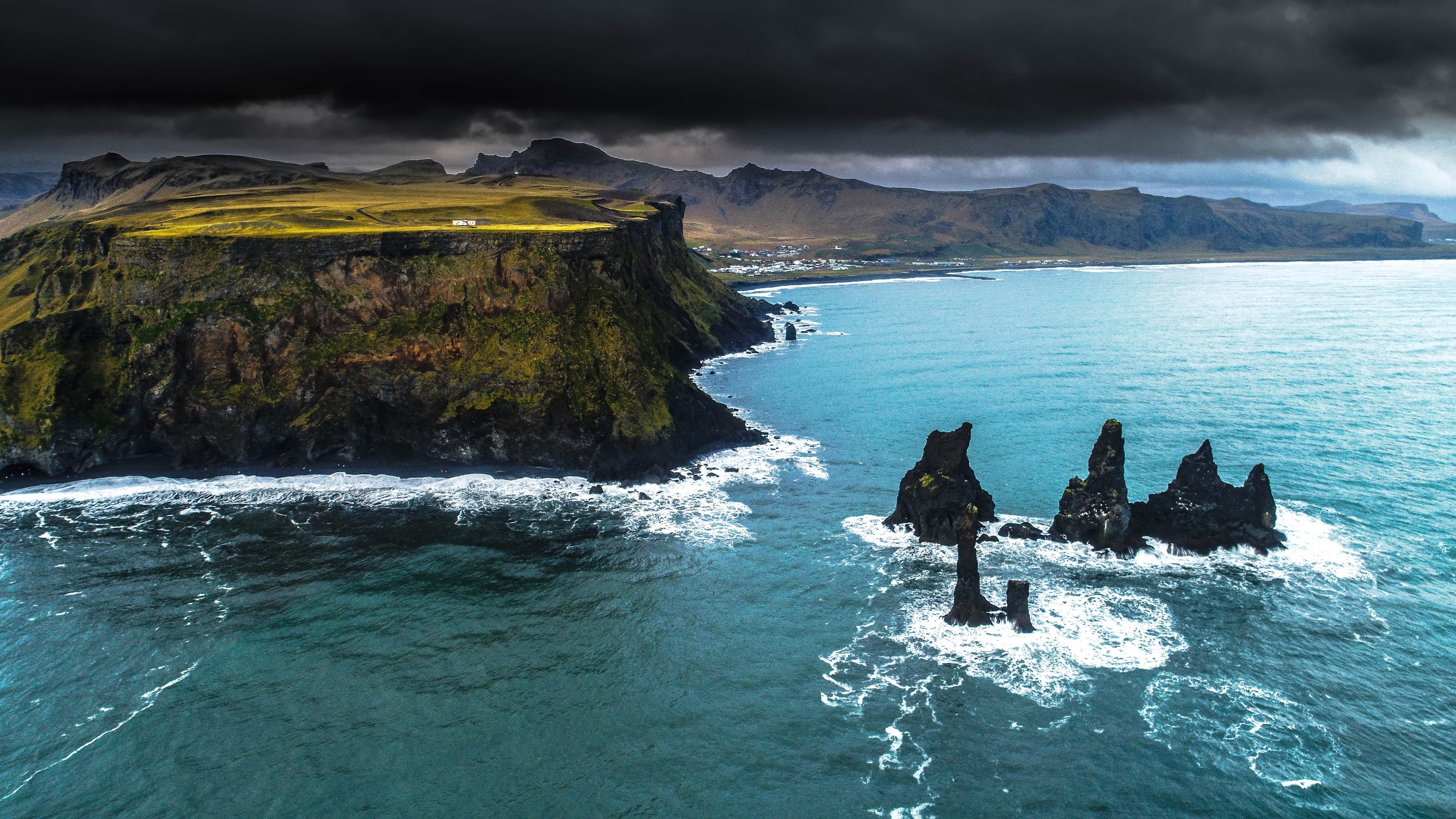 black sea stacks surrounded by body of water beside mountain under cloudy sky