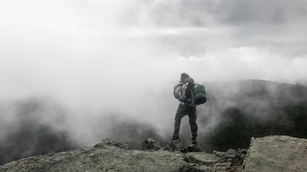 person carrying black hiking bag