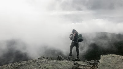 person carrying black hiking bag new hampshire teams background