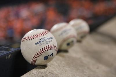 three white baseballs on gray textile baseball teams background