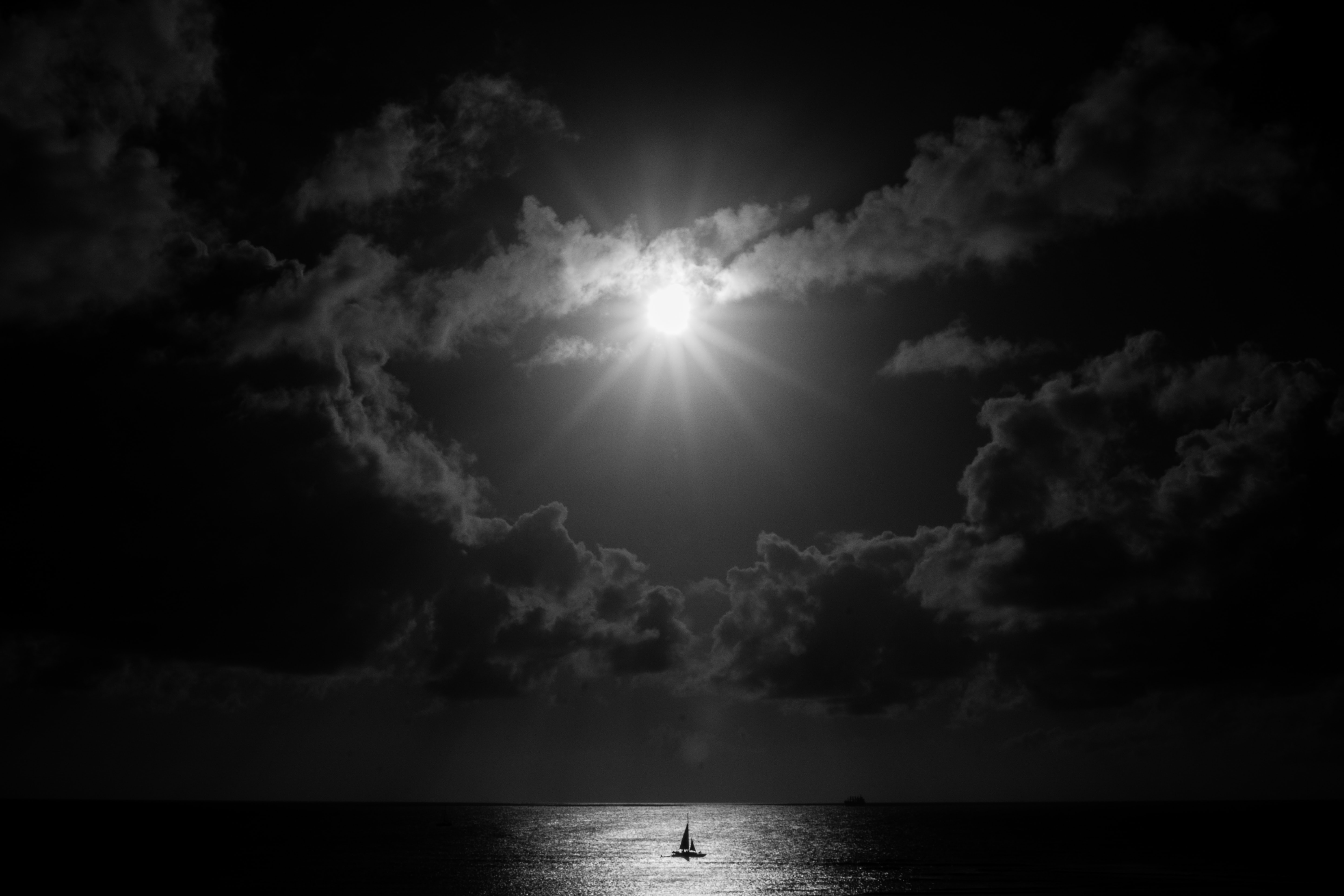 grayscale photo of body of water under sky