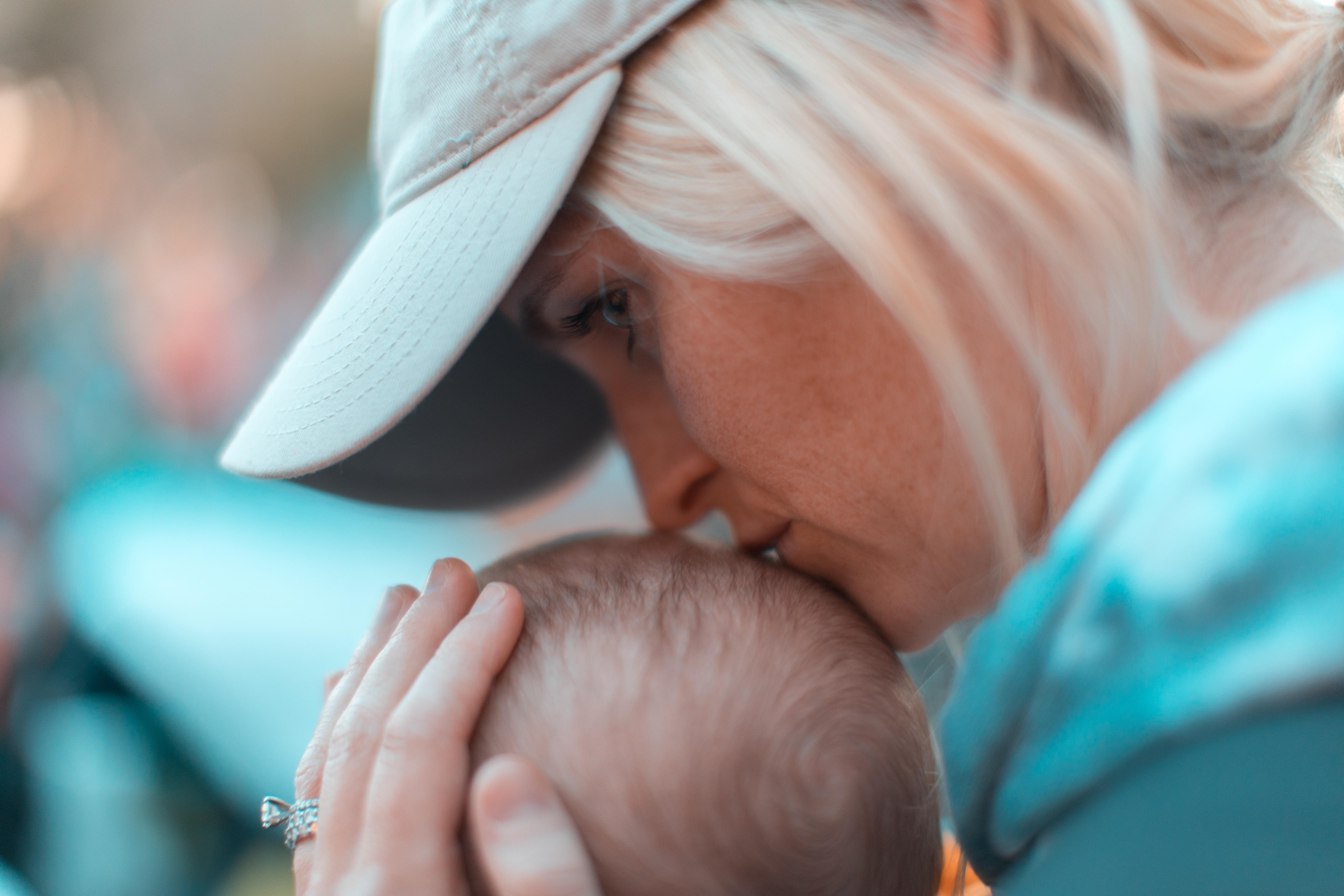 macro photography of woman kissing baby head