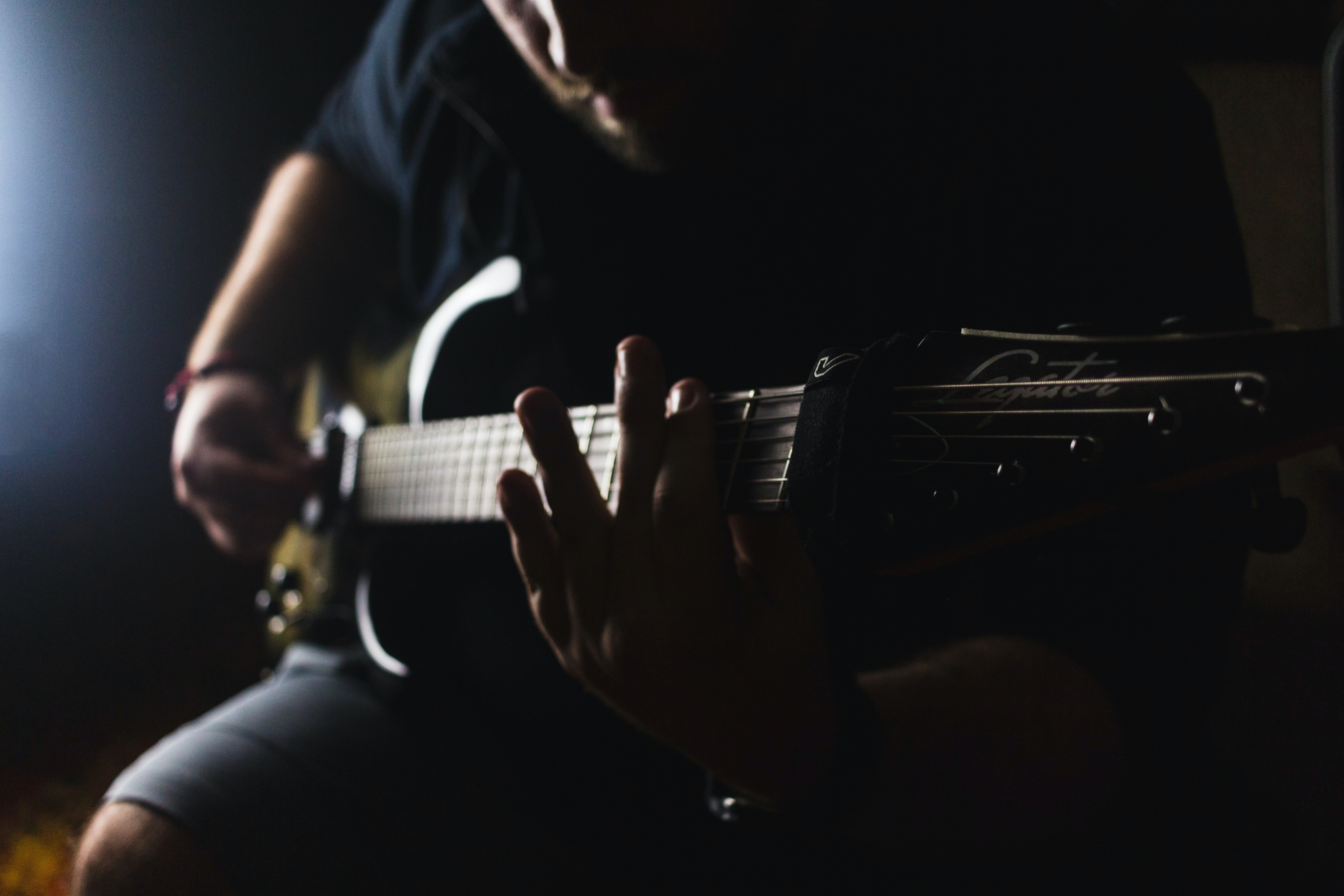 low light photography of man playing guitar