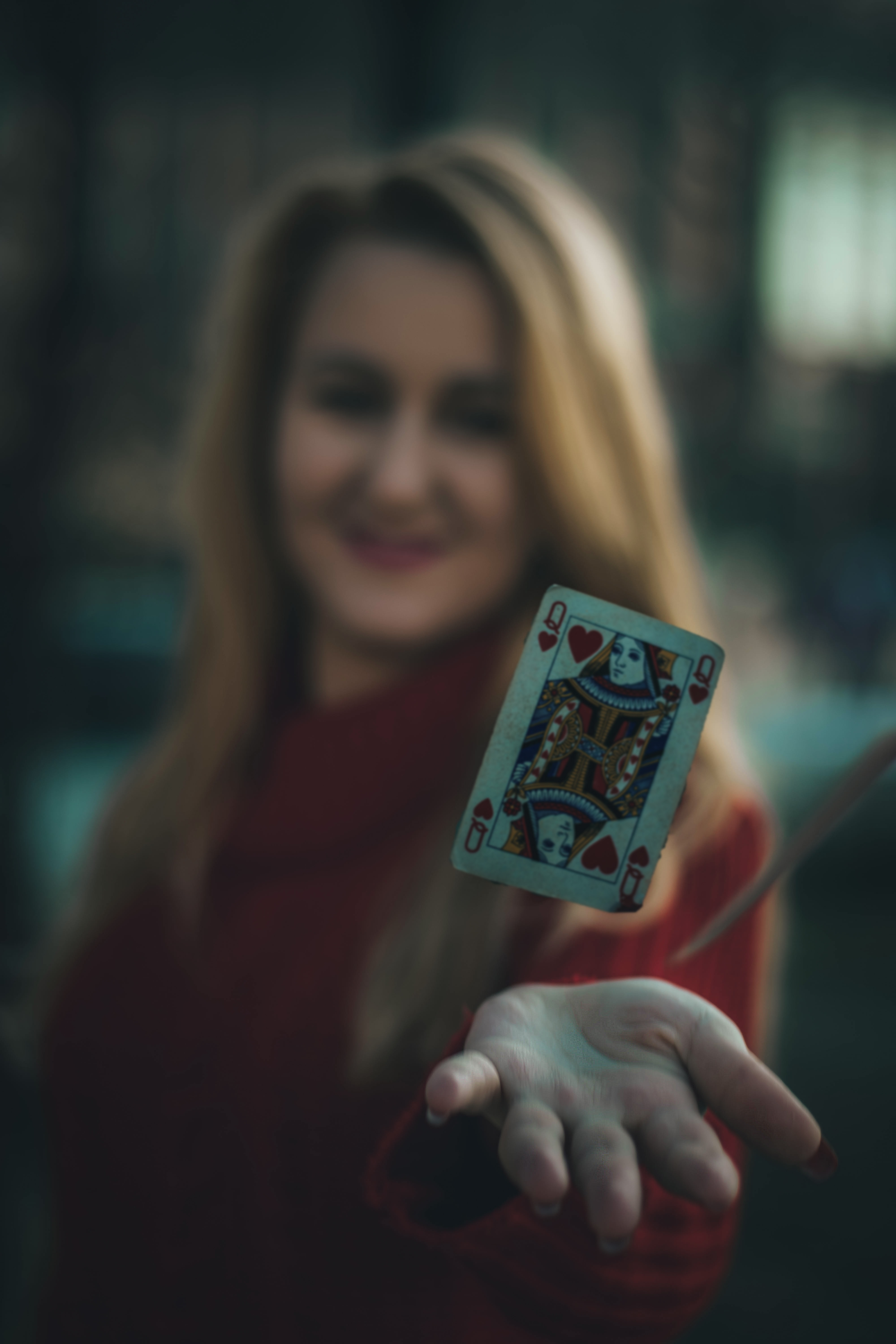 time lapse photo of queen of hearts playing card near woman's palm