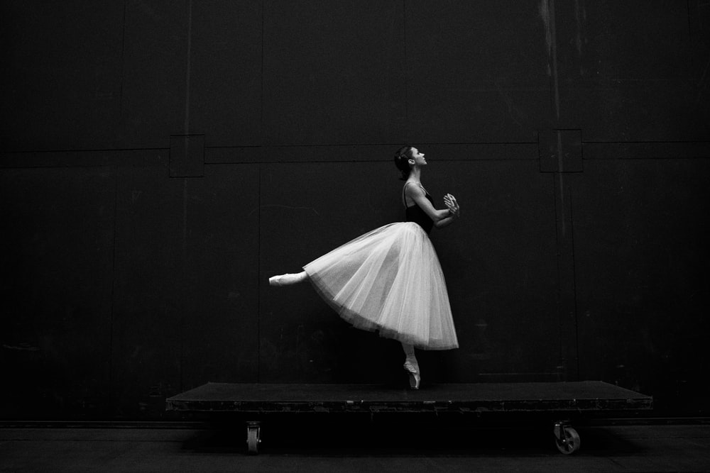 grayscale photography of ballet dancer standing on board