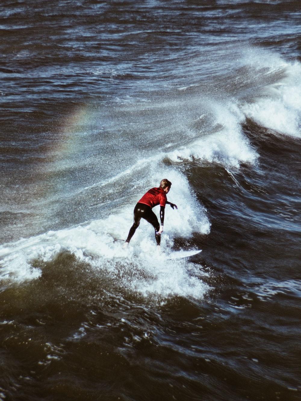 man riding surfboard on sea waves