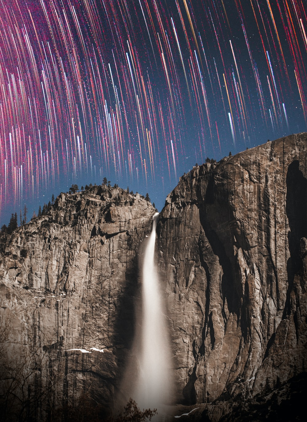 time lapse photography of stars and waterfalls
