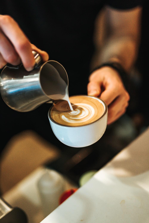 person preparing latte with art
