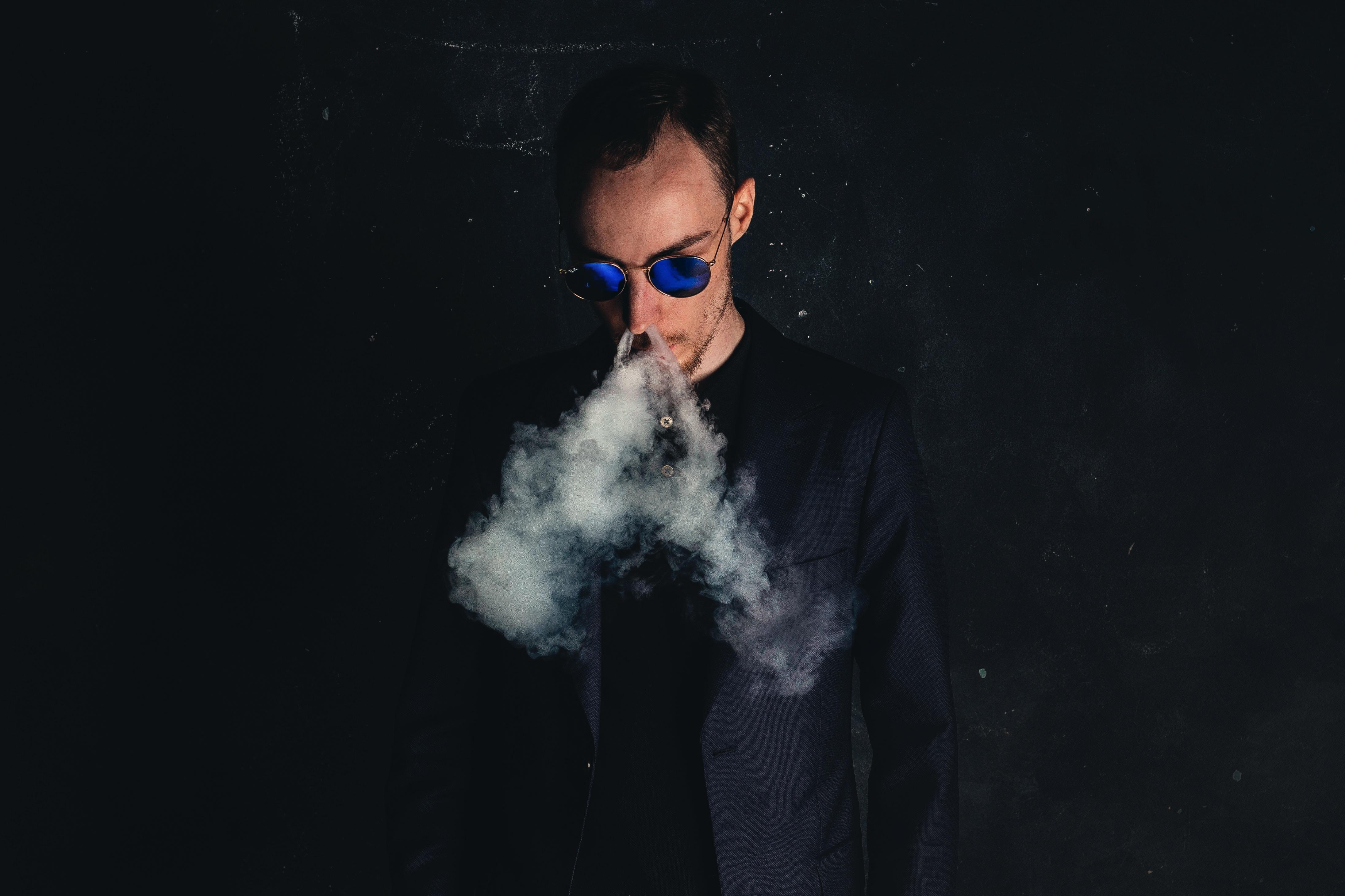 man in black suit jacket smoking