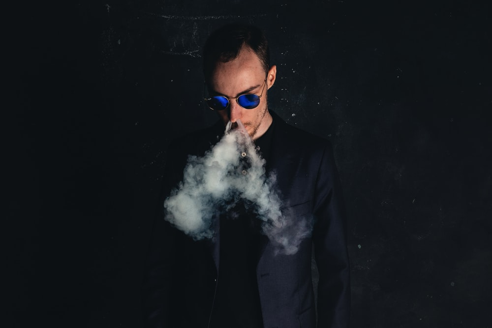 man in black suit jacket smoking
