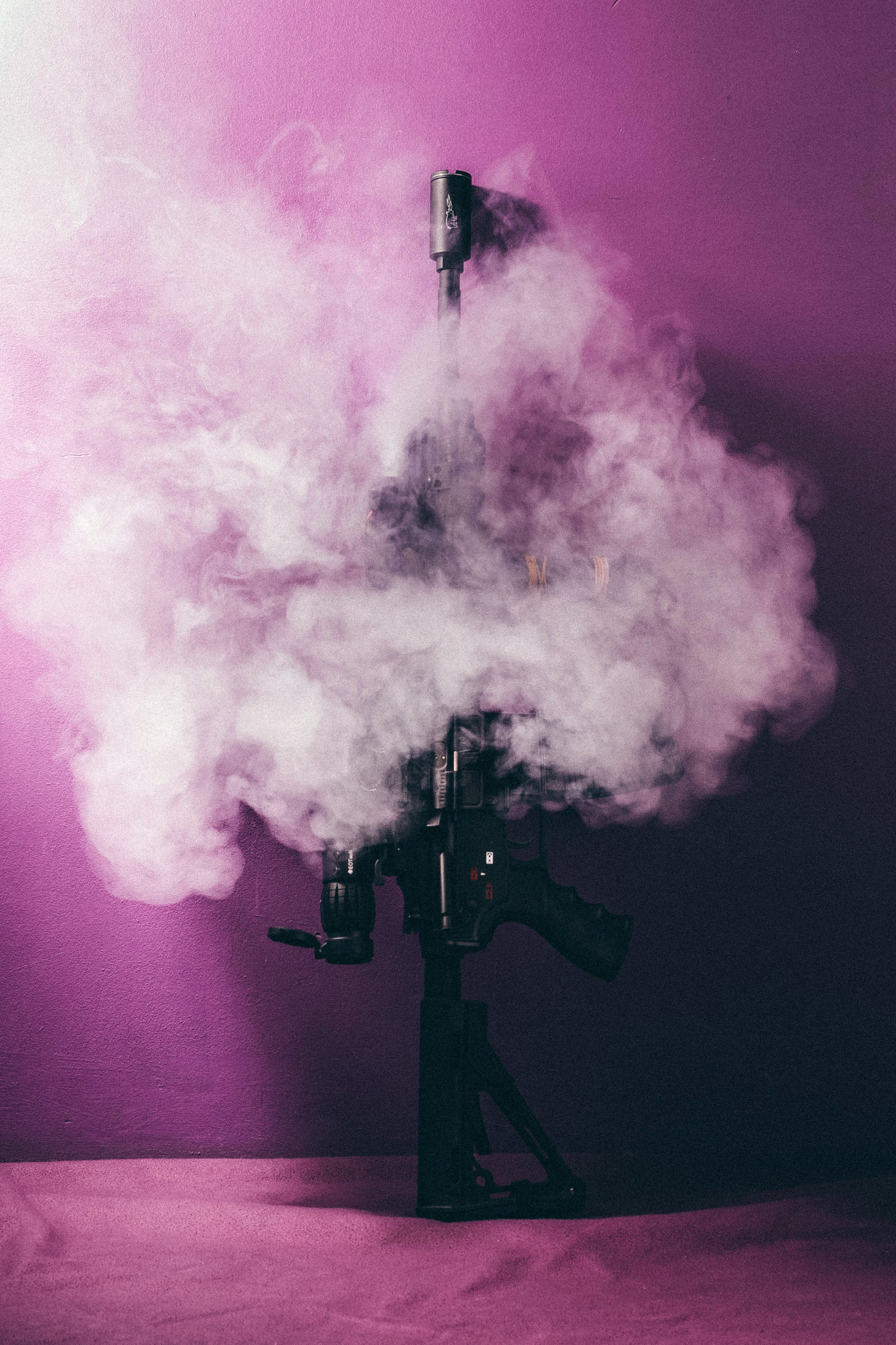 black assault rifle surrounded by smokes