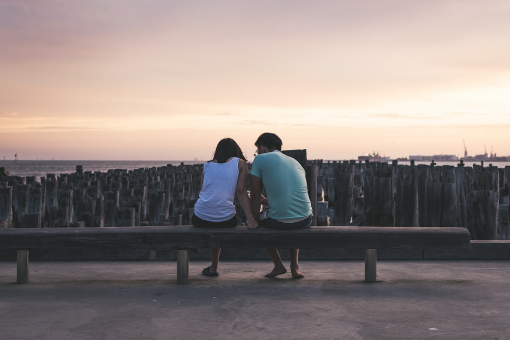 man and woman sitting on bench facing on body of water