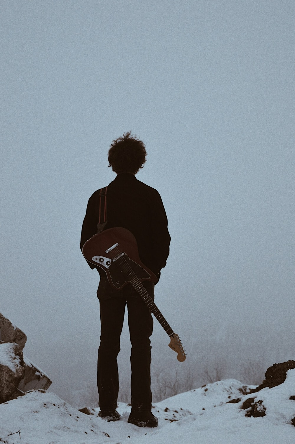 man with guitar on his back standing on cliff