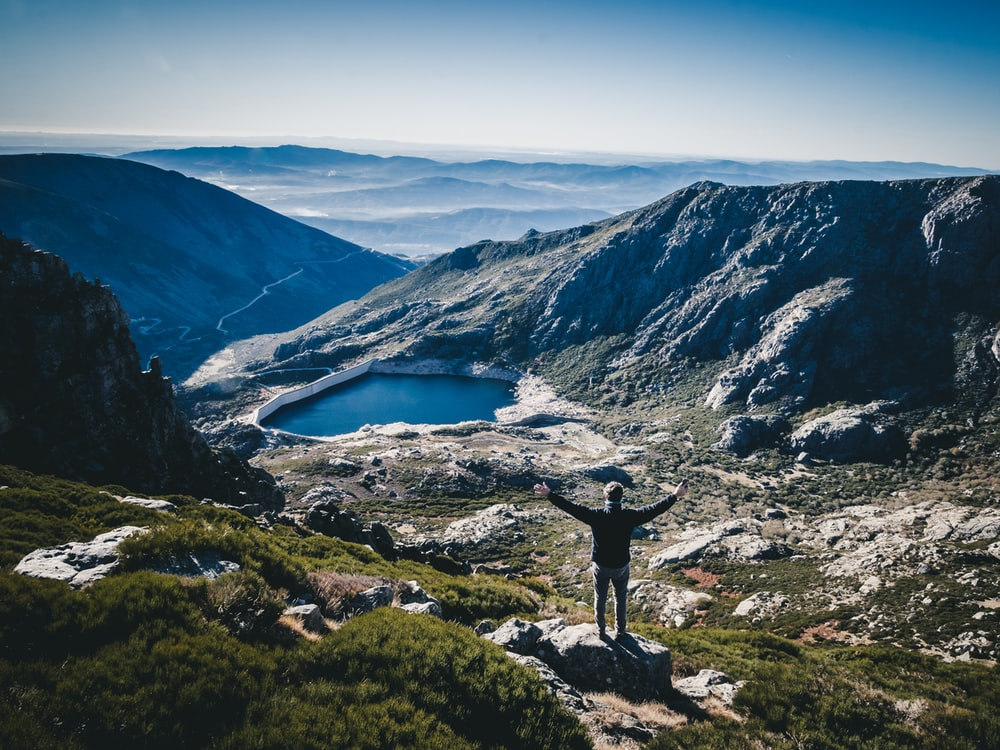 man standing on top of rock facing mountain