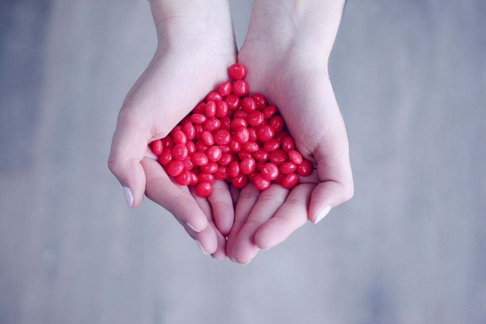 person holding red candies on her palms