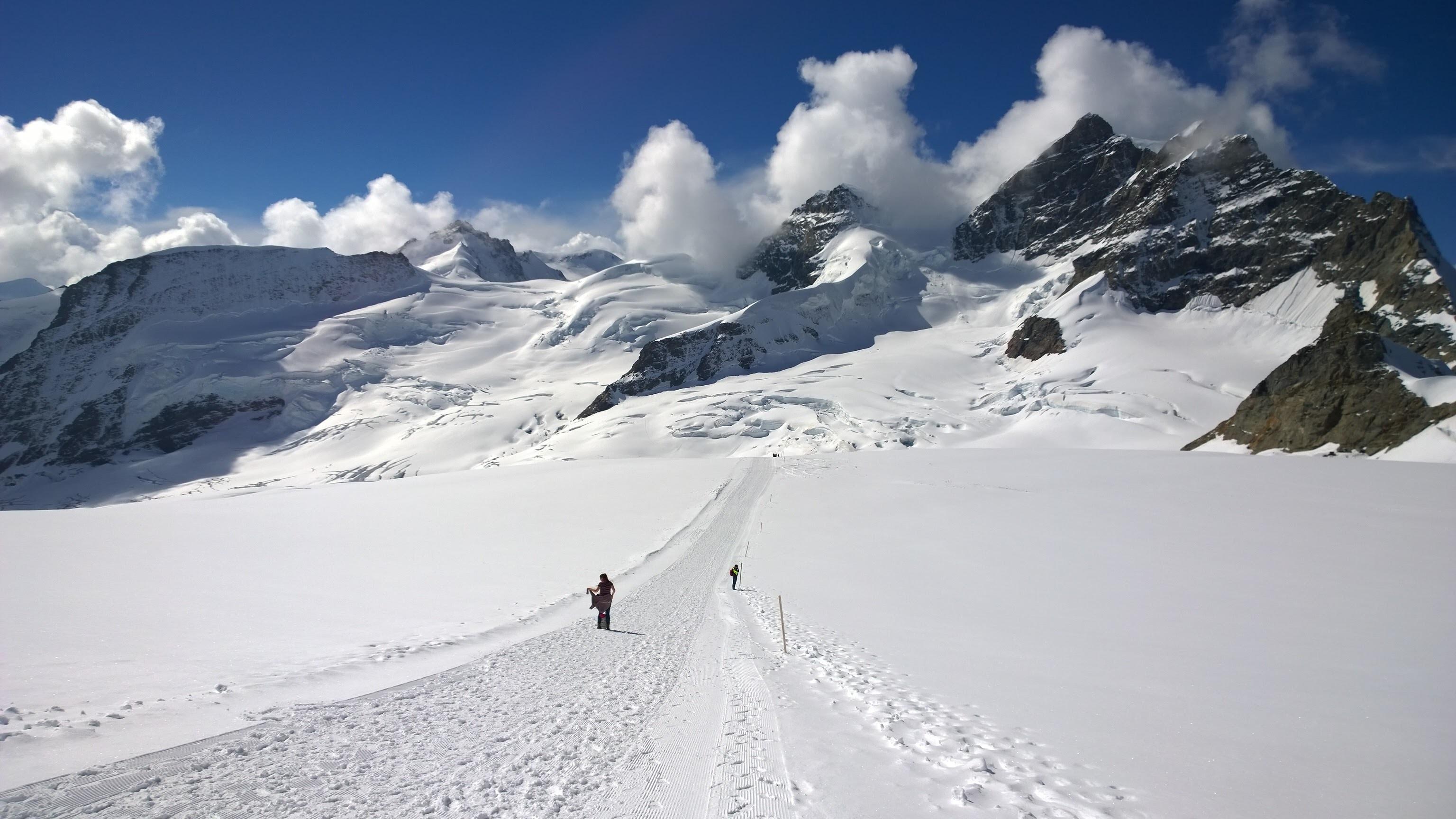 man walking through snowy mountain