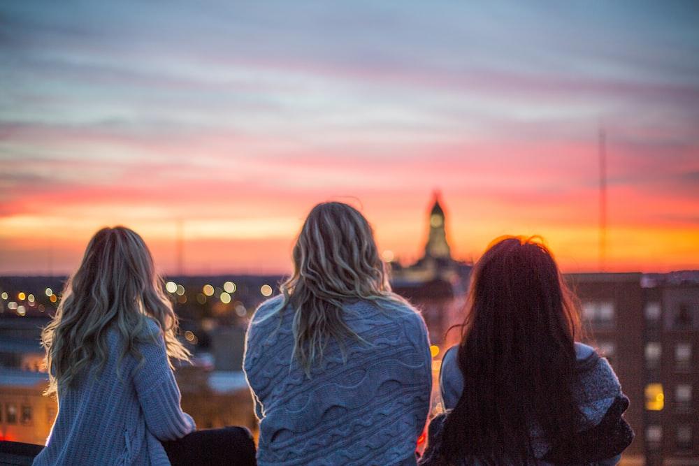 photo of three woman facing backward staring at horizon