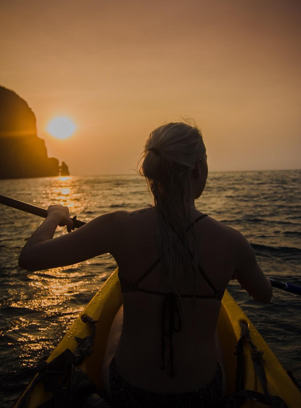 woman kayaking facing sunset
