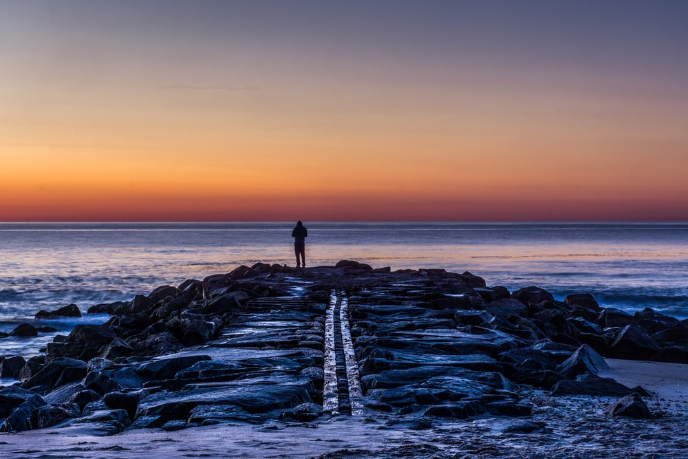 person standing on rocks silhouette