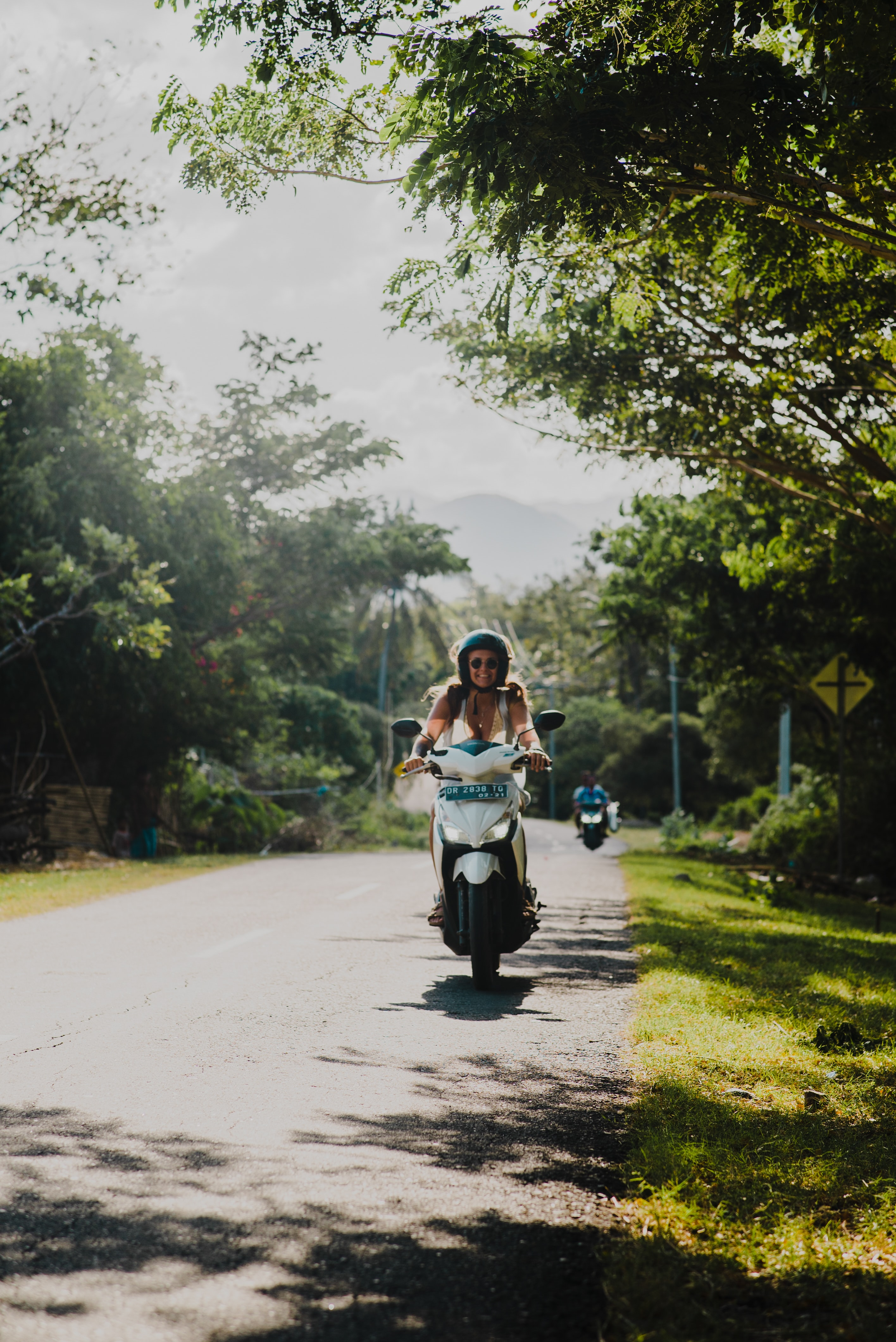 shallow focus photography of woman driving motorcycle at the road