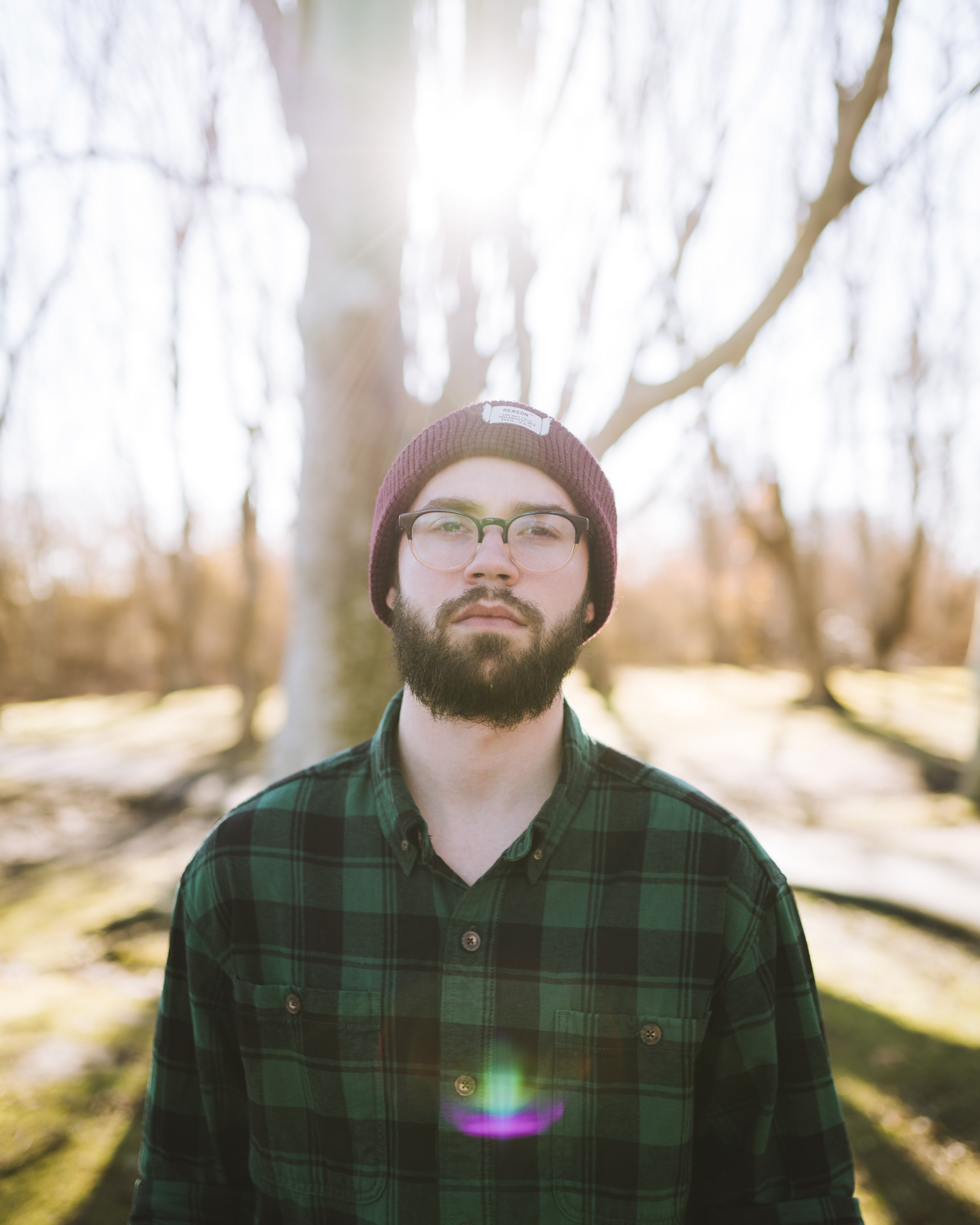 shallow focus photography of man standing near trees